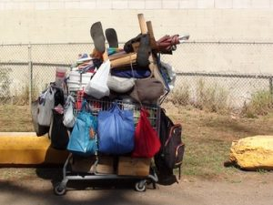 Homeless person's shopping cart filled w/belongings